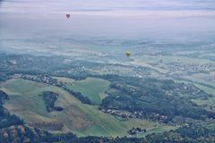 Foggy rural country scenery with balloons. Landscape with blue mist and pair of hot air balloons Royalty Free Stock Photos