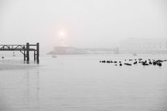 Foggy sea landscape with lighthouse. Foggy sea bay with pier and luminous lighthouse at background royalty free stock photos