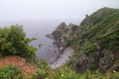 Foggy sea scape. Rocky shore. Royalty Free Stock Images