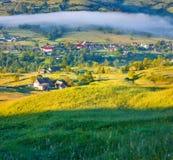 Foggy summer morning in mountain village. Stock Photos