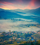Foggy summer morning in the mountain village. Stock Image