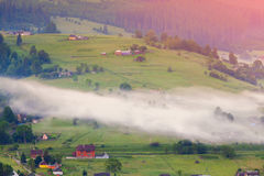 Foggy summer sunrise in mountain village Stock Images