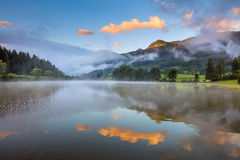 Foggy Sunrise on lake, with beautiful clouds and reflection Stock Photos