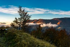 Foggy sunrise in mountainous countryside. Beautiful autumn scenery with trees, fences and red foliage on a hill in glowing fog under the blue sky Stock Photography