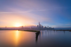 Foggy Sunrise from Newport Marina in Jersey City. This is a sunrise on a foggy day capturing Lower Manhattan in the background and a pier from the Newport  in Stock Image