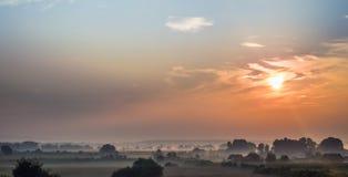 Foggy sunrise over village Royalty Free Stock Image