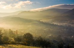 Foggy sunrise over the village in valley Royalty Free Stock Photography