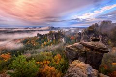 Foggy sunrise in the Saxon Switzerland, Germany, view from the Bastei lookout point. Royalty Free Stock Images