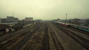 Foggy sunrise at a train station. With unrecognizable people walking on the platform time lapse stock video footage