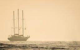 Foggy sunset sailboat at sea Royalty Free Stock Images