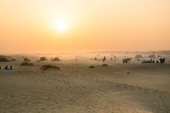 Foggy sunset in thar desert with camels on horizon. Foggy sunset in the thar desert in Rajasthan with people and camels visible on the horizon. Sum is a very Stock Photos