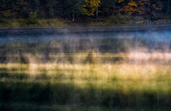 Foggy surface of the forest lake at sunrise Stock Image
