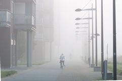 Foggy Town. A cyclist riding through the fog Stock Photo