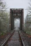 Foggy Train Bridge. Perspective photo of train tracks and bridge taken on a foggy day Stock Photo