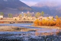 A foggy valley with a river. Some China west style architecture and trees look so beautiful in the sunlight of morning royalty free stock images
