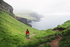 Foggy view of Mykines island with tourist in red jacket