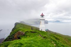 Foggy view of old lighthouse on the Mykines island