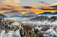 Foggy village under the mountains in winter. At dawn royalty free stock photo