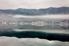 Foggy weater on the sea with mountain reflections Royalty Free Stock Images