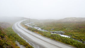 Foggy weather. A country road over foggy mountain in Norway Stock Image