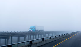 Foggy weather on foggy highway big rig semi truck trailer driving carrying cargo logistic moving on concrete bridge. Modern big blue rig semi-truck with a royalty free stock photo
