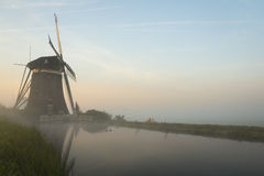 Foggy windmills on a dike Royalty Free Stock Images