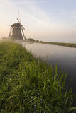 Foggy windmills on a dike Royalty Free Stock Photography