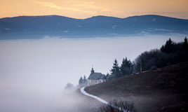Foggy winter dusk with chapel on the hillside Stock Image
