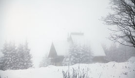 Foggy winter landscape with mountain cottage Stock Image