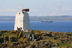Foghorn on island with passing ship Stock Photo