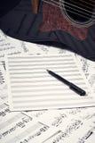 Fogli bianchi per le note, la penna e la chitarra fotografie stock libere da diritti