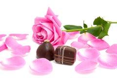 Fogli della rosa di colore rosa con i bonbon del cioccolato Fotografia Stock