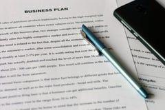 Fogli di carta bianchi con testo stampato sulla tavola con una penna blu e uno smartphone nero Verifica dei rendiconti finanziari fotografie stock libere da diritti