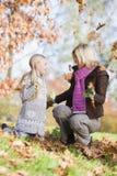 Fogli di lancio della figlia e della madre nell'aria Fotografia Stock