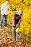 Fogli felici di raccolto delle coppie di autunno in sosta Fotografia Stock