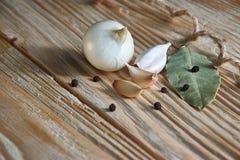 Foglia, cipolla ed aglio di alloro sul piano d'appoggio di legno Preparato asciutto delle spezie Immagini Stock