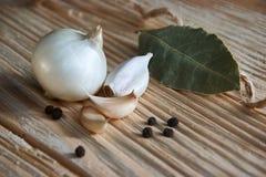Foglia, cipolla ed aglio di alloro sul piano d'appoggio di legno Preparato asciutto delle spezie Fotografie Stock