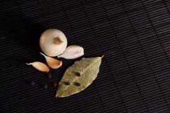 Foglia, cipolla ed aglio di alloro sul piano d'appoggio nero Preparato asciutto delle spezie Fotografia Stock Libera da Diritti