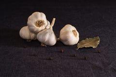 Foglia, cipolla ed aglio di alloro sul piano d'appoggio scuro del tessuto Preparato asciutto delle spezie Immagine Stock