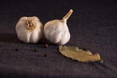 Foglia, cipolla ed aglio di alloro sul piano d'appoggio scuro del tessuto Preparato asciutto delle spezie Fotografie Stock