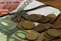 Foglia della sospensione di marijuana, monete, euro banconote Fotografia Stock