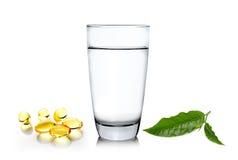 Foglia di tè di verde del wiith del bicchiere d'acqua ed olio di pesce sul whi Fotografia Stock Libera da Diritti