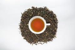 Foglia di tè secca e la tazza bianca di tè sui precedenti bianchi Fotografie Stock Libere da Diritti