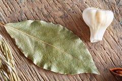 Foglia ed aglio di alloro organici sul bordo di legno, vista superiore, primo piano, fuoco selettivo Fotografia Stock