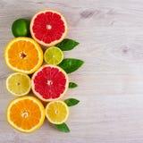 Foglia succosa della menta del fondo del taglio degli agrumi Arance, limoni, calce, pompelmo, foglie di menta su un fondo di legn Fotografia Stock Libera da Diritti