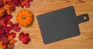 Fogliame di autunno con una zucca e una lavagna Fotografia Stock Libera da Diritti