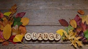 Foglie cambianti su legno con il CAMBIAMENTO delle lettere Fotografia Stock