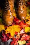 Foglie di autunno bagnate e vecchie scarpe sul terrazzo di legno Fotografia Stock
