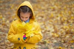Foglie di autunno della tenuta della bambina Fotografia Stock Libera da Diritti