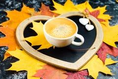 Foglie di autunno e tazza di caff? sulla tavola Composizione nella foglia di autunno con la struttura a forma di del cuore Copi l fotografia stock libera da diritti